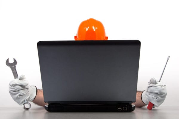 Maintenance person sitting behind laptop holding a wrench and screwdriver preparing to participate in a CMMS software demo.