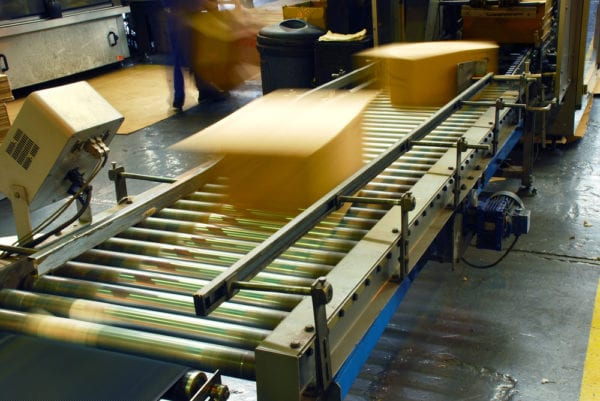 Boxes on a conveyor belt being moved at a rapid speed demonstrating an increase in production due to competition