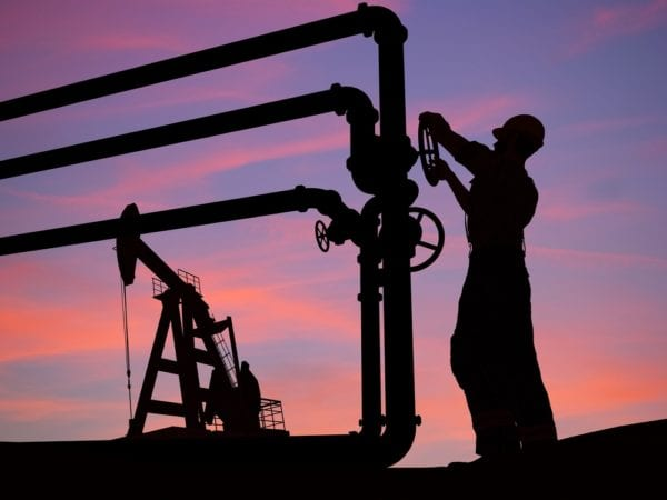 A technician closes the valve on the tube of an oil pump at dusk in accordance with regulatory compliance tasks assigned in a CMMS.
