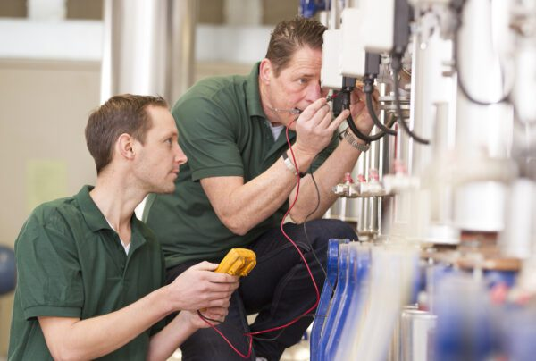 A young male technician looks on as an older male technician uses a voltmeter to check the calibration of production equipment as part of an MRO activity.