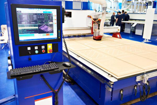 CNC machine in a furniture factory engraving wood to represent production equipment that requires repair as part of MRO.