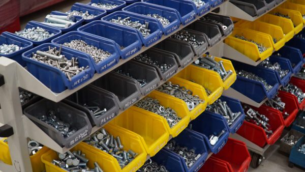 Storage bins for nuts, bolts, and screws in a stockroom to represent MRO tools and consumables.
