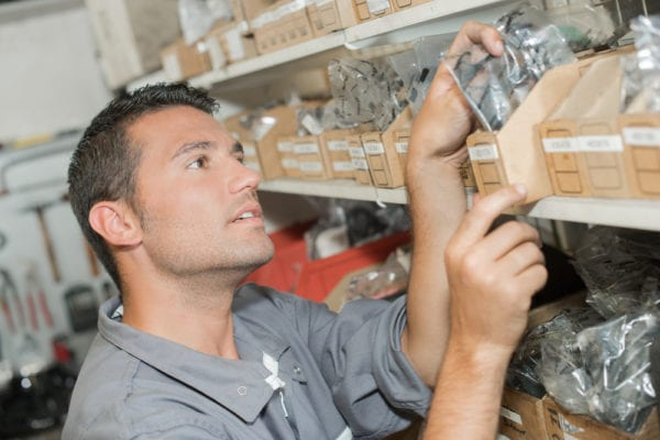 Young maintenance technician choosing parts from a storeroom as identified on a bill of materials for an asset in need of repair