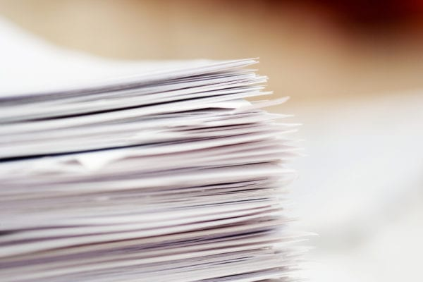 Stack of paper work orders, focused on the corner of the stack