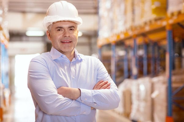 Middle-aged business man wearing a white hard hat smiling while standing in a warehouse representing upper management to whom you may need to justify the cost of cmms software.
