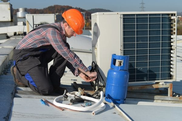 Maintenance technician performing corrective maintenance repair on an air conditioning unit