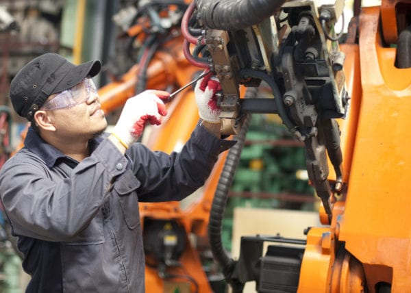A young mechanic executing a work order for the repair of a robotic machine as part of the work order management process