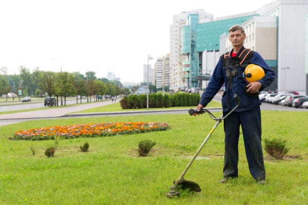 A middle-aged male facility maintenance tech with a gas trimmer standing on the lawn of a corporate property