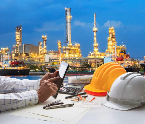 Business person working on a computer tablet against a factory background, researching the difference between CMMS and EAM software.