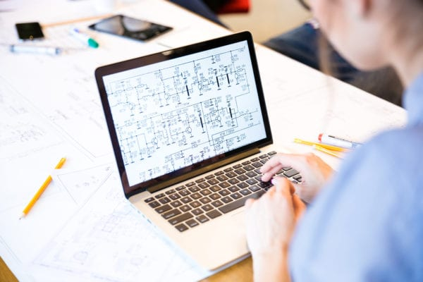 floor-plan-software-complex-laptop-woman-typing-replace-cmms