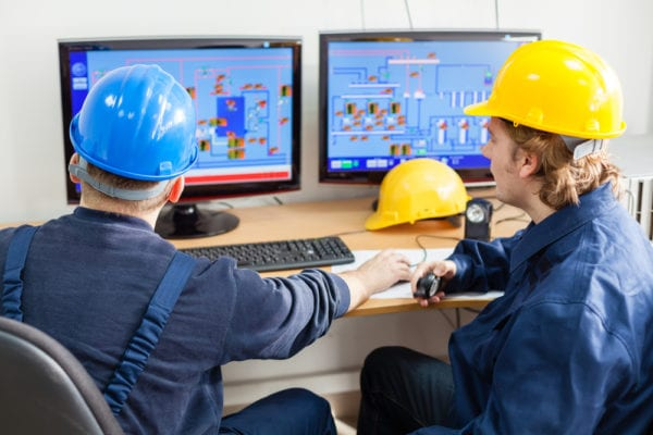 two technicians-hard hats-floor plans- computer-cost of unplanned downtime