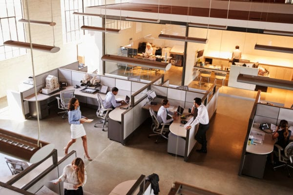 High angle view of a busy open office plan that benefits from proper facility management.