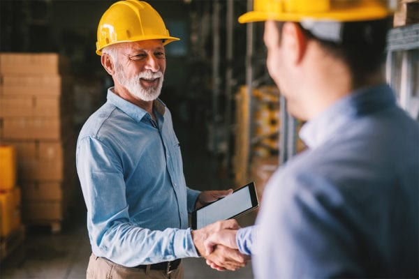 Two business casual men representing CMMS stakeholders standing in warehouse with helmets on their heads shaking hands