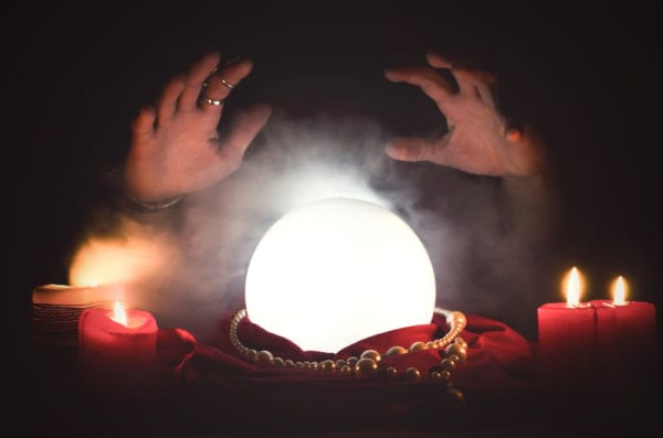 A fortune teller hovering her hands over an illuminated crystal ball attempting to predict maintenance needs.