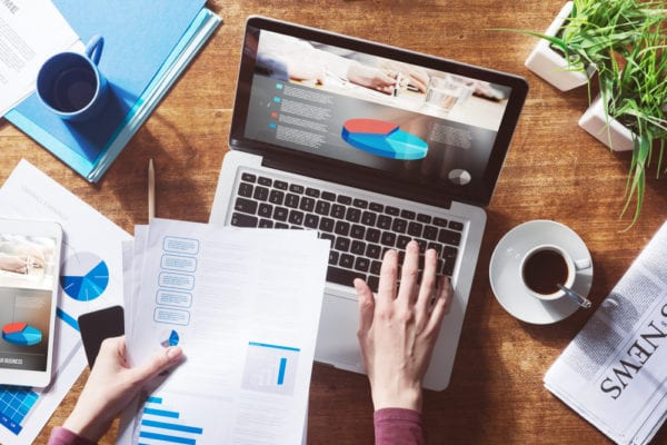 laptop-chart-paperwork-data transfer-coffee cups-desk