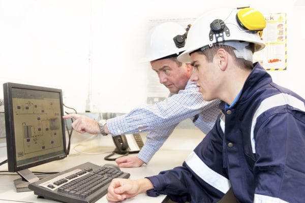 Older and younger men in hard hats discussing work together, older man pointing to area on a computer screen displaying failure codes.