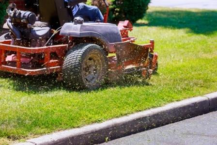 A person on a riding mower do summer maintenance by cutting the lawn.