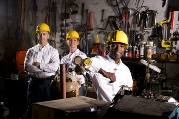 Three diversified employees in hard hats in a garage to represent maintenance department culture.