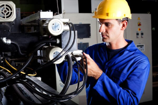 Young male technician inspecting a machine to gather information and identify potential problems to troubleshoot.
