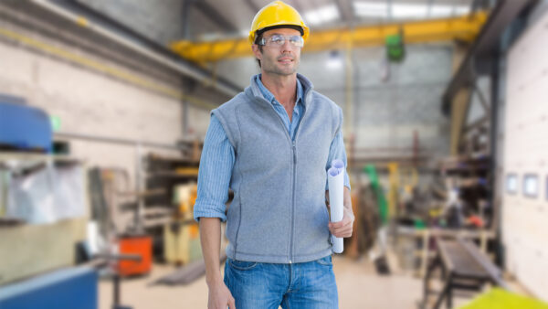 Middle-aged maintenance worker, selected a the project leader to implement a proactive maintenance plan, standing in a maintenance workshop.