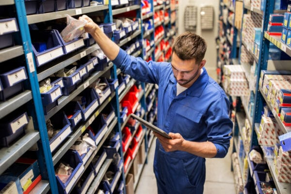 Young male stockroom worker auditing stock quantities as a first step in defining benchmarks for inventory management KPIs.
