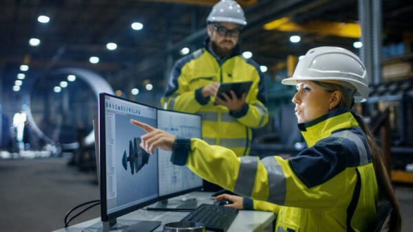 Man with tablet and woman on desktop pointing to screen with hard hats, managing maintenance work.
