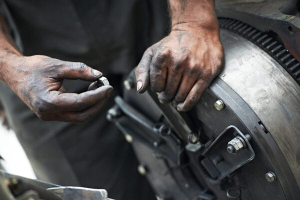 Mechanics hands examining a worn component, described on an equipment bill of materials (EBOM), in order to assess the severity of a machine's condition.
