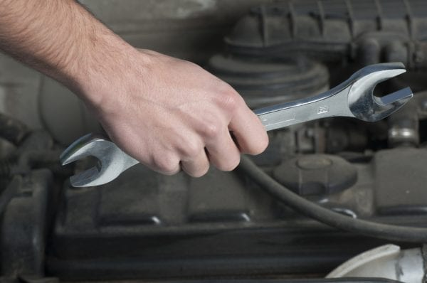 A male hand holding a crescent wrench tool in front of a motor.