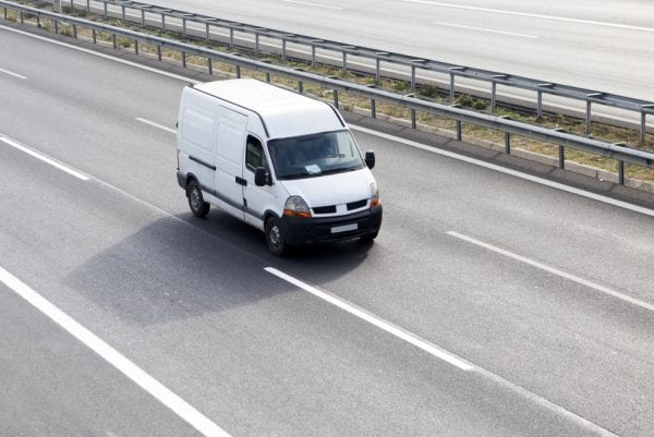A sprinter van vehicle asset driving in the middle lane of a highway.