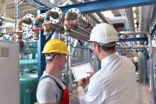 Two young male technicians looking at asset data on a tablet near some piping to help identify whether the asset is critical and should be included in the organization's preventive maintenance program.
