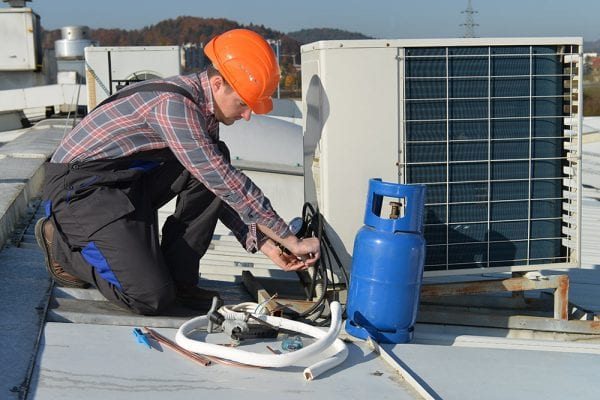 Young male HVAC technician performs preventive maintenance on a rooftop air handling unit as part of the organization's PM program.