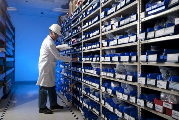 Maintenance worker checking inventory on a stockroom shelf to demonstrate the company's inventory control techniques.