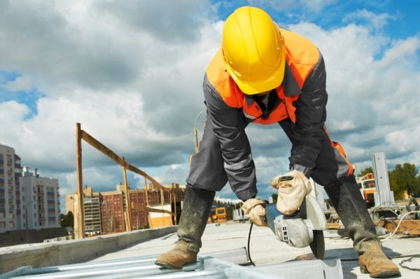 A construction worker in a hard hat using a concrete saw.