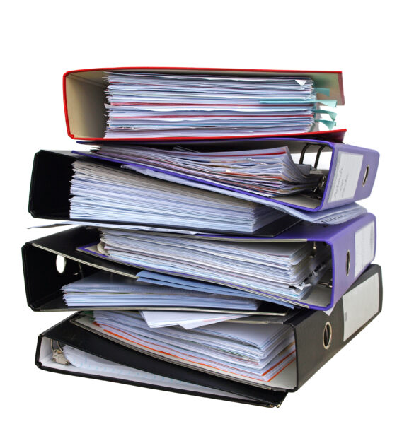 A stack of thick binders to represent the ISO 9001 and materials referenced to create the ISO 9001 manual.