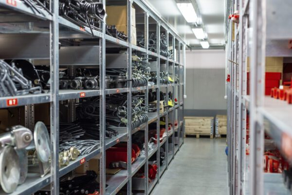 An organized maintenance storeroom showing large metal parts neatly organized on metal shelving in a clutter-free aisle.